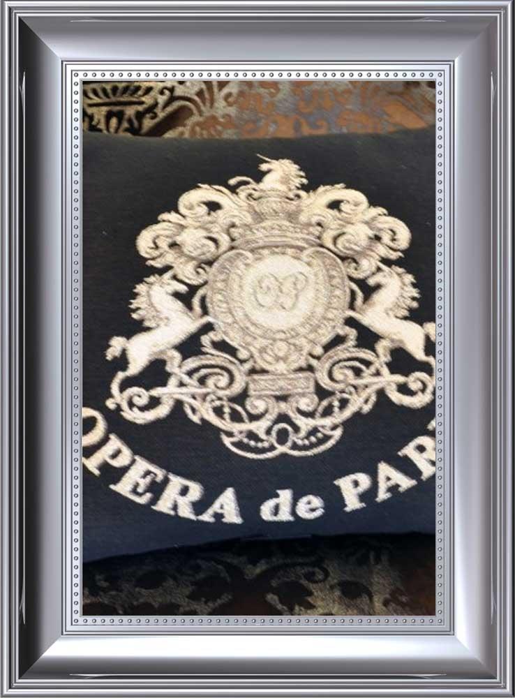 Ezüst színű fa keretben opera de paris gobelin címer hímezve.