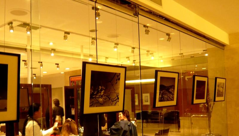 Képfüggesztő rendszer használata fodrász üzletben. A képeket a tükör fal elé, a tükör megfúrása nélkül, lehet felakasztani.