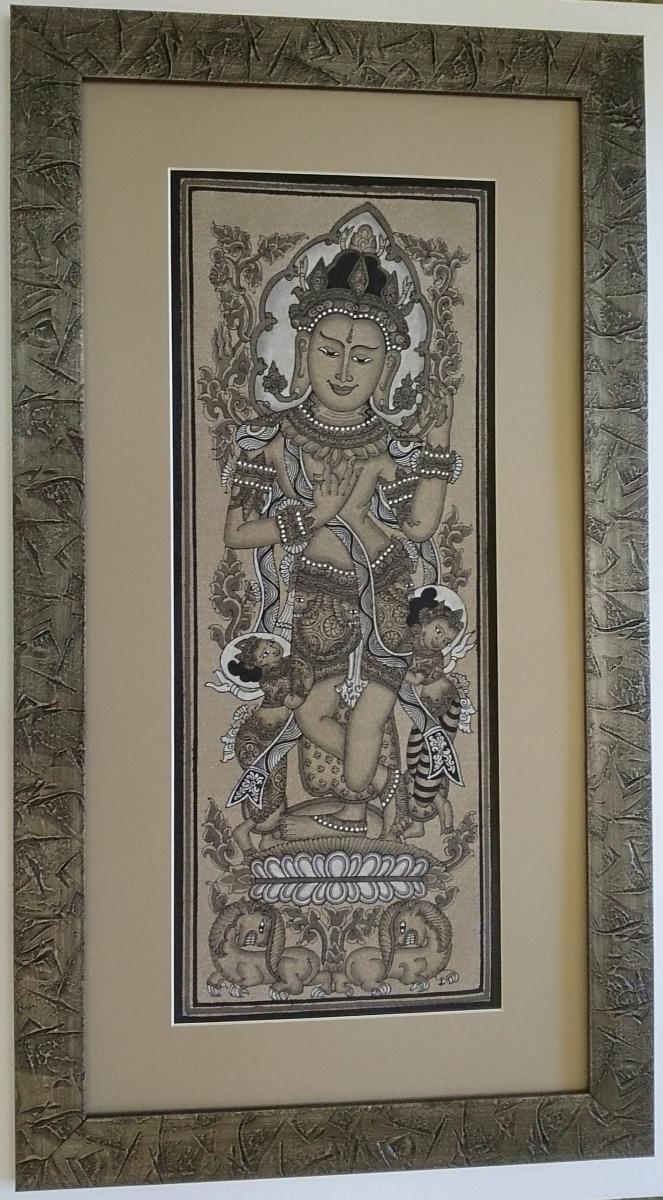 Ázsiai istennő ábrázoló színezett homokkal készített alkotásának képkeretezése, kőhatású, kobalt színű fa képkeretbe.